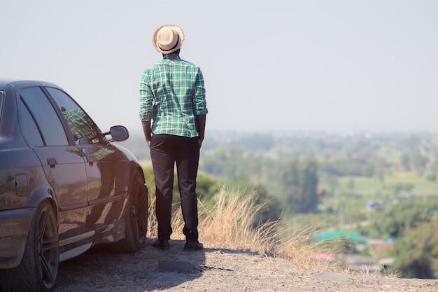 Afrykańska mężczyzna pozycja na górze rockowej falezy z samochodem
