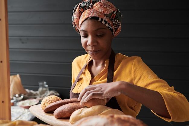 Afrykańska młoda kobieta biorąca świeży chleb, który pracuje w sklepie piekarniczym