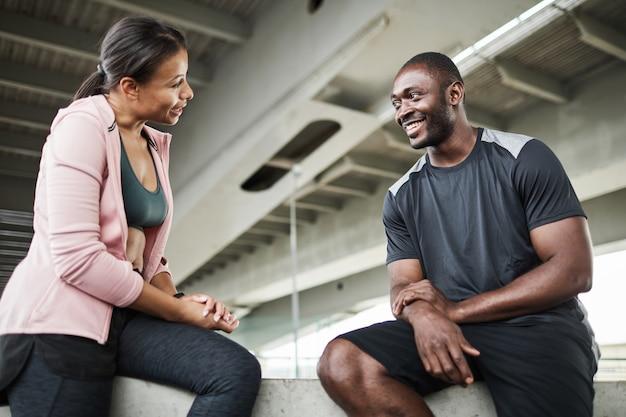 Afrykańska młoda kobieta omawia trening sportowy ze swoim instruktorem, gdy siedzą na siłowni