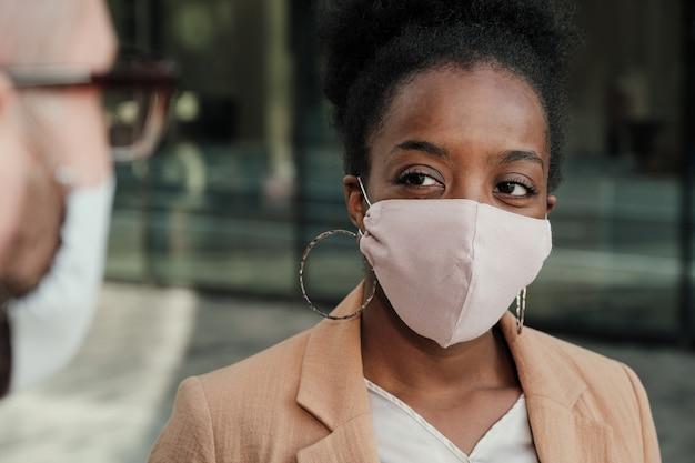 Afrykańska młoda kobieta w masce ochronnej, rozmawia z mężczyzną, stojąc na zewnątrz