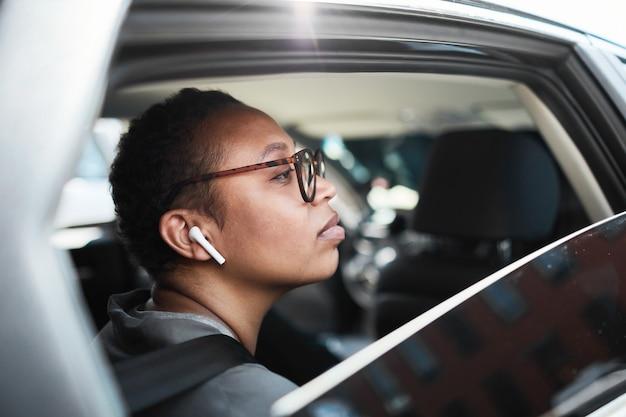 Afrykańska młoda kobieta w okularach i słuchawkach bezprzewodowych patrząca przez okno siedząc w samochodzie