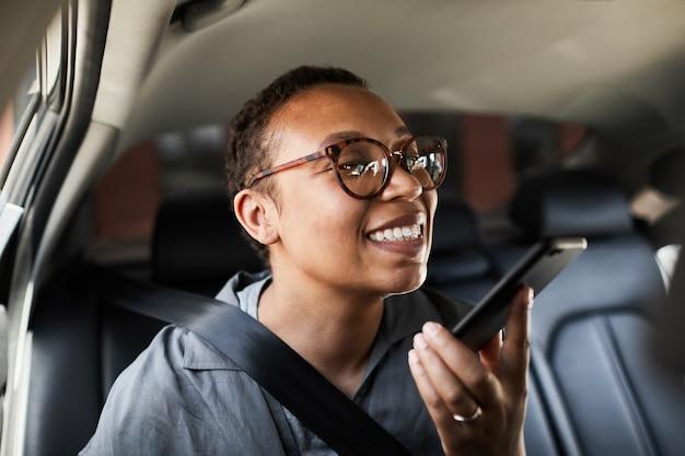 Afrykańska młoda kobieta w okularach nagrywająca wiadomość audio na swoim telefonie komórkowym podczas jazdy samochodem