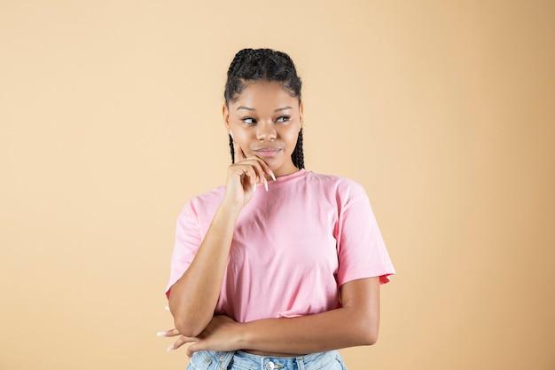 Afrykańska młoda kobieta z zamyśloną twarzą i palcem na geście twarzy, poziome zdjęcie