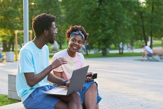 Afrykańska młoda para pracuje razem na laptopie podczas ich spotkania w parku