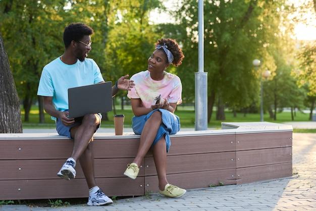 Afrykańska młoda para siedzi na ławce w parku, używając laptopa i rozmawiając