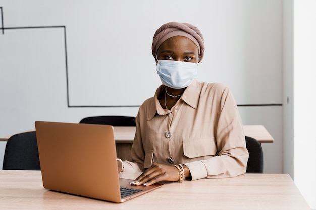 Afrykańska murzynka z laptopem. korzystanie z komputera do pracy on-line. maska medyczna do ochrony przed koronowirusem covid-19.