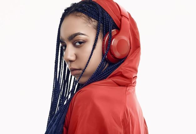 Afrykańska nastoletnia dziewczyna z dreadlocks w czerwonym wiatrówka słucha muzykę