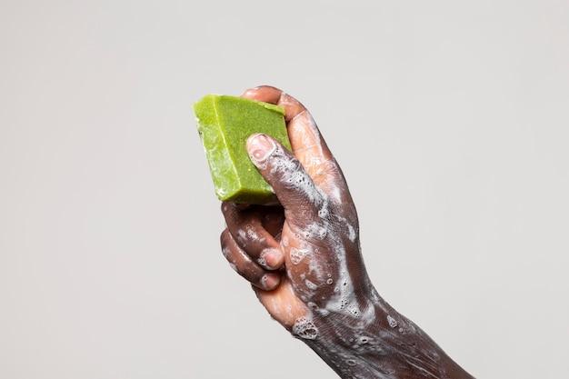 Afrykańska osoba myjąca ręce mydłem na białym tle