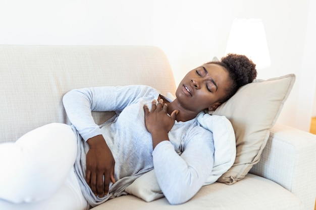 Afrykańska piękna kobieta chora na ból w klatce piersiowej leżąc na kanapie.