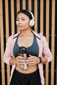 Afrykańska piękna kobieta w bezprzewodowych słuchawkach trzymająca butelkę wody podczas treningu na świeżym powietrzu