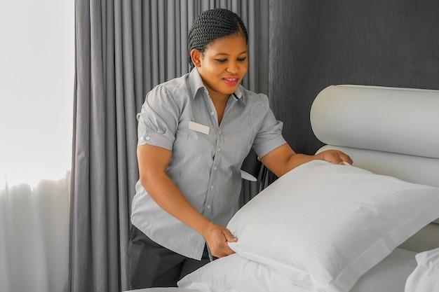 Afrykańska pokojówka ścielenie łóżka w pokoju hotelowym.
