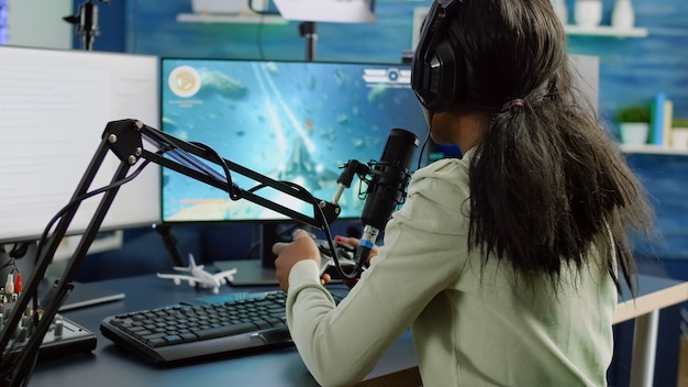 Afrykańska streamerka rozmawiająca z zespołem w słuchawkach i wygrywająca konkurs gier wideo