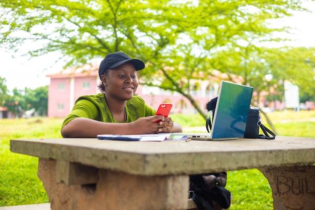 Afrykańska studentka używająca telefonu komórkowego do czytania w kampusie