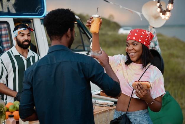 Afrykańska szczęśliwa para je fast food i tańczy podczas imprezy na świeżym powietrzu