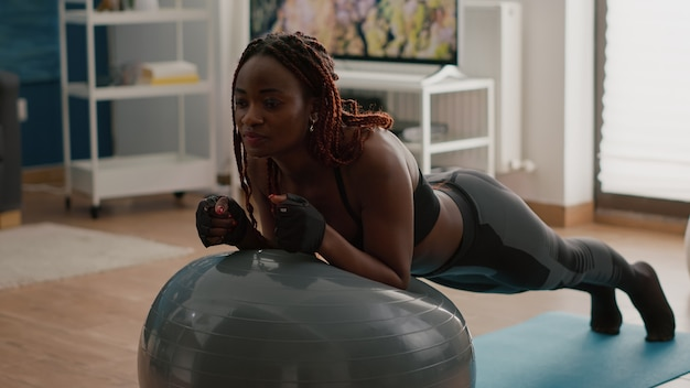 Afrykańska szczupła kobieta rozciągająca mięśnie brzucha siedząc na szwajcarskiej piłce jogi podczas porannego treningu w salonie