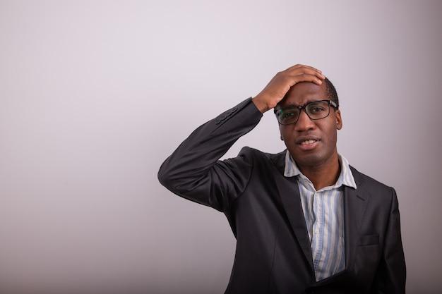Afrykański biznesmen ma zdezorientowany wyraz twarzy, kładzie rękę na głowie i jest zdezorientowany. mężczyzna z okularami i zagubionym wyrazem twarzy, skopiuj miejsce po lewej stronie tej osoby