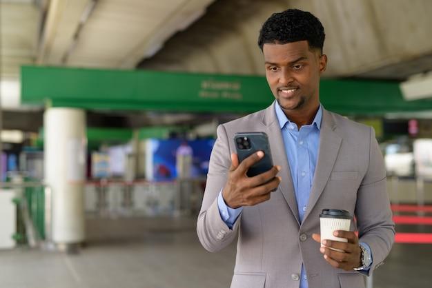Afrykański biznesmen na zewnątrz niosący filiżankę kawy na wynos, uśmiechając się i używając telefonu komórkowego mobile