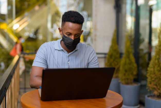 Afrykański biznesmen nosi maskę na twarz i dystansuje się, siedząc w kawiarni przy użyciu laptopa laptop