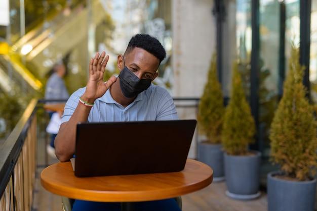 Afrykański biznesmen noszący maskę na twarz i dystansujący się, siedząc w kawiarni przy użyciu laptopa i prowadząc wideorozmowę podczas uśmiechania się