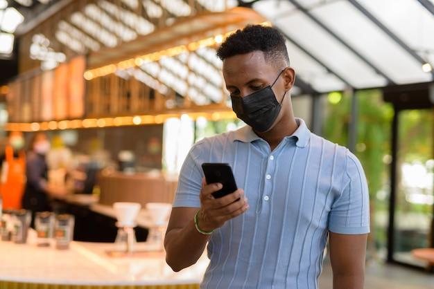 Afrykański biznesmen noszący maskę w kawiarni podczas dystansu społecznego i korzystania z telefonu komórkowego