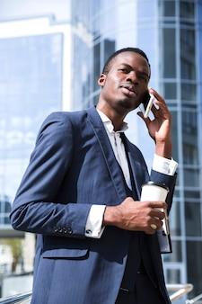 Afrykański biznesmen opowiada na telefonie komórkowym trzyma jednorazową filiżankę kawy