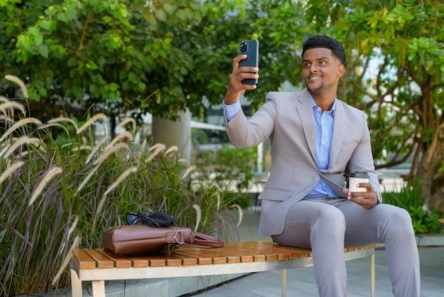 Afrykański biznesmen siedzący na zewnątrz, trzymający filiżankę kawy na wynos i używający telefonu komórkowego do robienia selfie