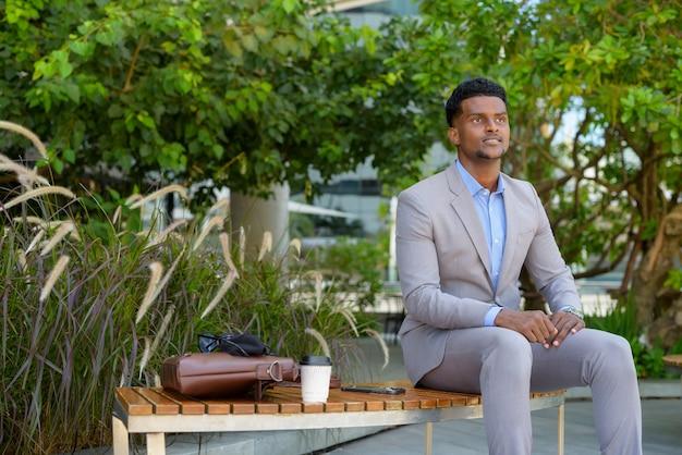 Afrykański biznesmen siedzi na zewnątrz, uśmiechając się i myśląc