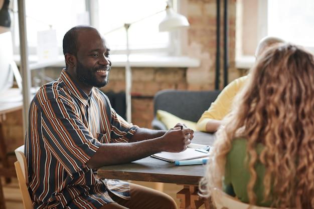 Afrykański biznesmen siedzi przy stole i uśmiecha się, rozmawiając ze swoimi kolegami na spotkaniu biznesowym w biurze