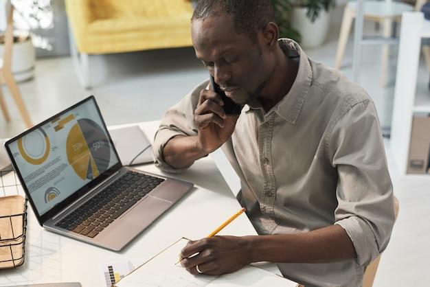 Afrykański biznesmen siedzi przy stole z laptopem i robi notatki w swoim notatniku podczas rozmowy przez telefon komórkowy