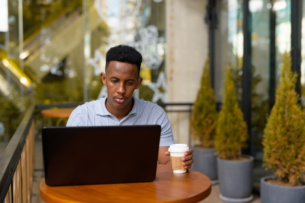 Afrykański biznesmen siedzi w kawiarni podczas korzystania z laptopa