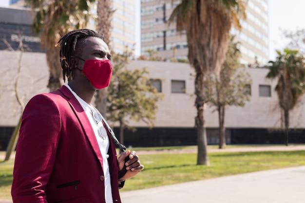 Afrykański biznesmen spacerujący po mieście z czerwoną maską pasującą do garnituru, koncepcja elegancji