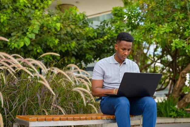 Afrykański biznesmen ubrany na co dzień i siedzący podczas korzystania z laptopa