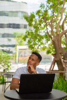 Afrykański biznesmen ubrany na co dzień i siedzący w kawiarni, myśląc i używając laptopa laptop