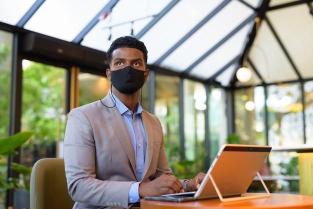 Afrykański biznesmen w kawiarni korzystający z laptopa i noszący maskę na twarz