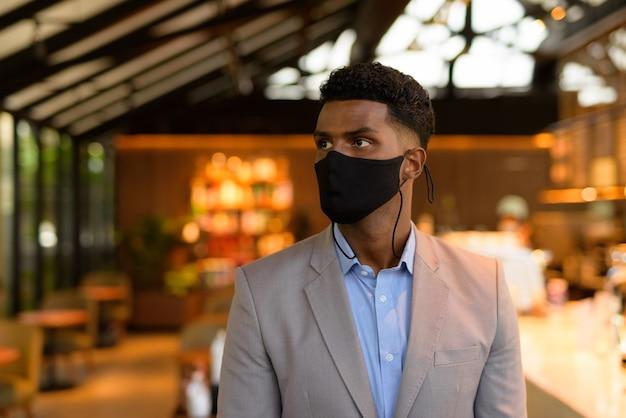 Afrykański biznesmen w kawiarni noszący maskę na twarz i dystans społeczny