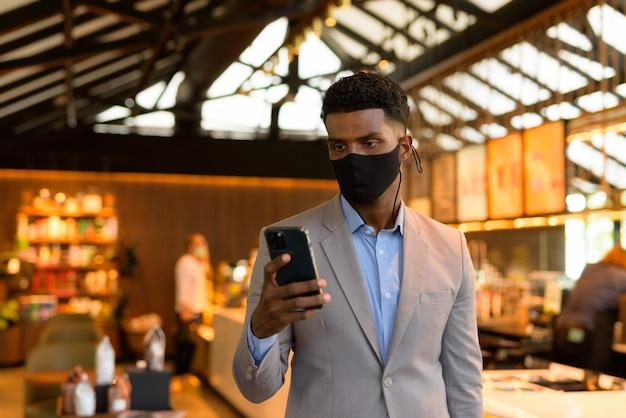 Afrykański biznesmen w kawiarni noszący maskę na twarz i używający telefonu komórkowego mobile