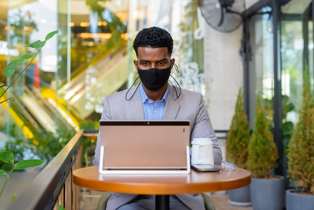 Afrykański biznesmen w kawiarni noszący maskę na twarz podczas dystansu społecznego i korzystania z laptopa
