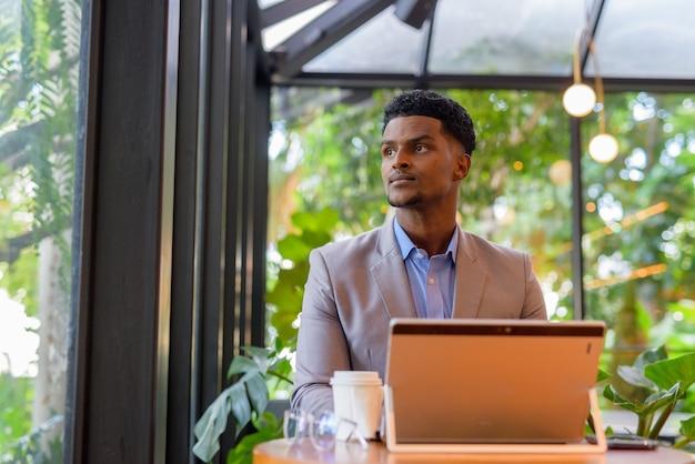 Afrykański biznesmen w kawiarni przy użyciu laptopa i myśląc patrząc przez okno