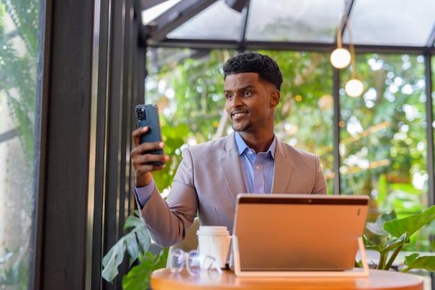 Afrykański biznesmen w kawiarni przy użyciu laptopa i robienia selfie z telefonem komórkowym