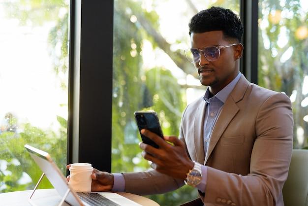 Afrykański biznesmen w kawiarni przy użyciu laptopa i telefonu komórkowego