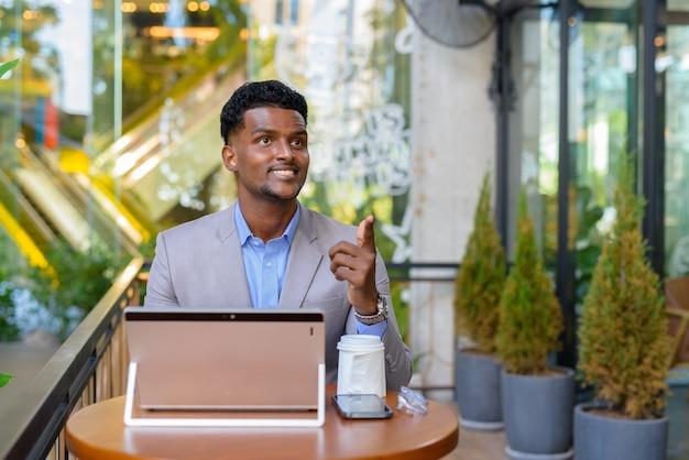 Afrykański biznesmen w kawiarni przy użyciu laptopa, uśmiechając się i wskazując palcem