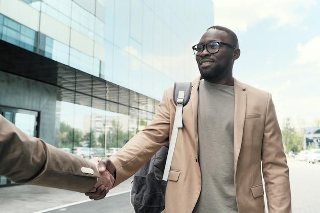 Afrykański biznesmen w okularach, ściskając rękę swojemu koledze, gdy oni stoją w mieście