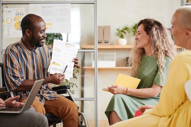 Afrykański biznesmen wskazujący na dokument finansowy w swoich rękach i wyjaśniający to swoim kolegom na spotkaniu