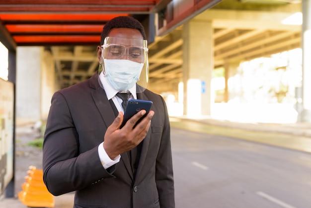 Afrykański biznesmen z maską i twarzy osłoną używać telefon przy autobusową przerwą w mieście outdoors