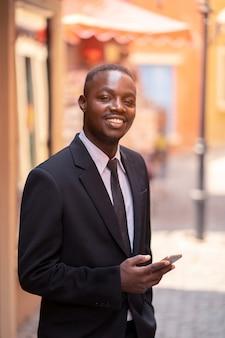 Afrykański biznesowy mężczyzna używa jego smartphone w mieście