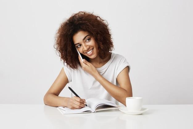 Afrykański bizneswoman ono uśmiecha się opowiadający na telefonie przy miejscem pracy. biała ściana.