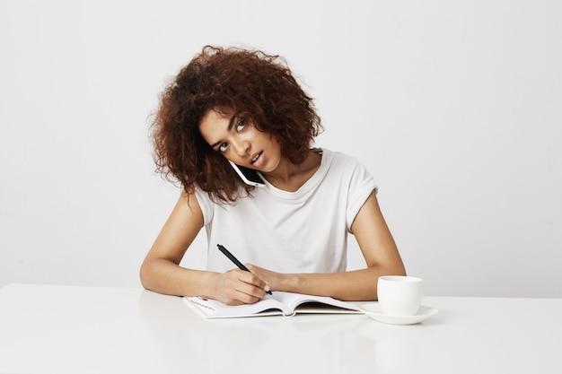 Afrykański bizneswoman opowiada na telefonie przy miejscem pracy nad biel ścianą. skopiuj miejsce