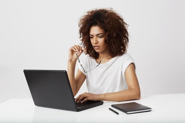Afrykański bizneswoman patrzeje laptopu ekran myśleć nad biel ścianą.