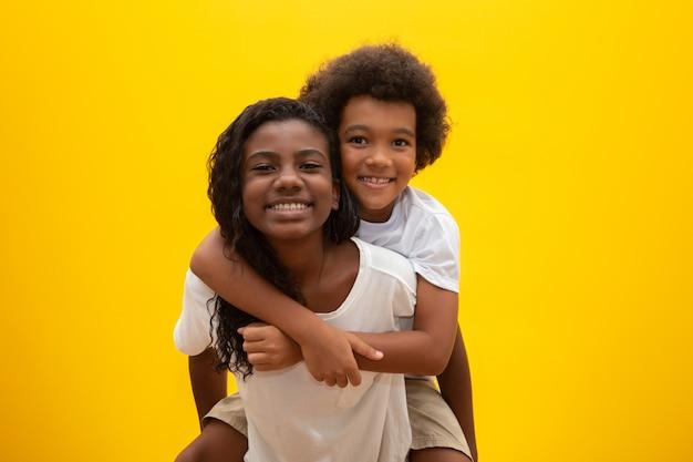 Afrykański brat i siostra. wiązanie rodzeństwa. uśmiechnięte czarne dzieci przytulanie.