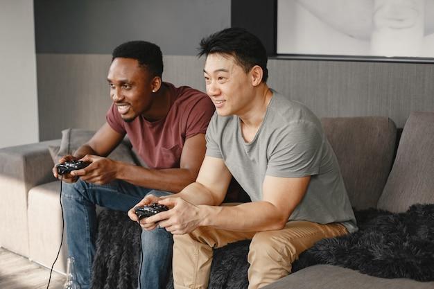 Afrykański chłopiec i azjatycki chłopiec siedzi na kanapie i gra na playstation. przyjaciele grają w gry w wolnym czasie za pomocą joysticka.